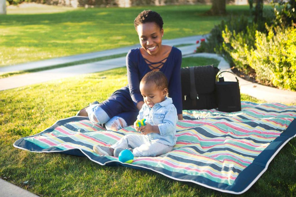 mother and baby laying on jj cole outdoor blanket