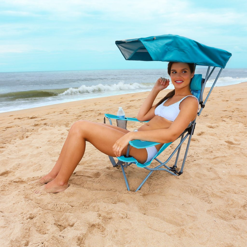 woman on the beach sitting in a folding canopy chair