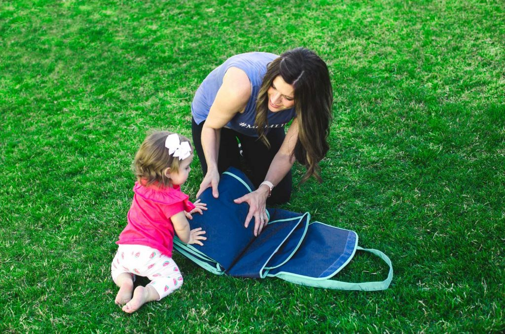 mom folding baby picnic blanket with her toddler