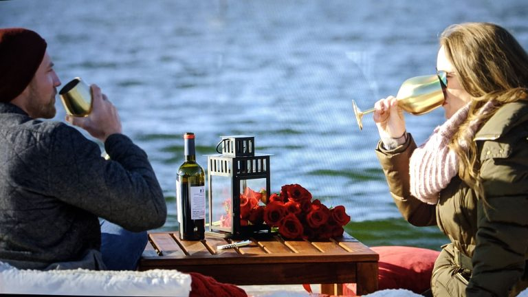 couple drinking wine from gold wine glasses
