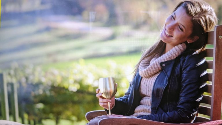 woman holding gold wine glass outside