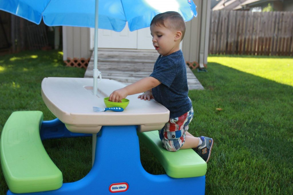 kid playing at small picnic table