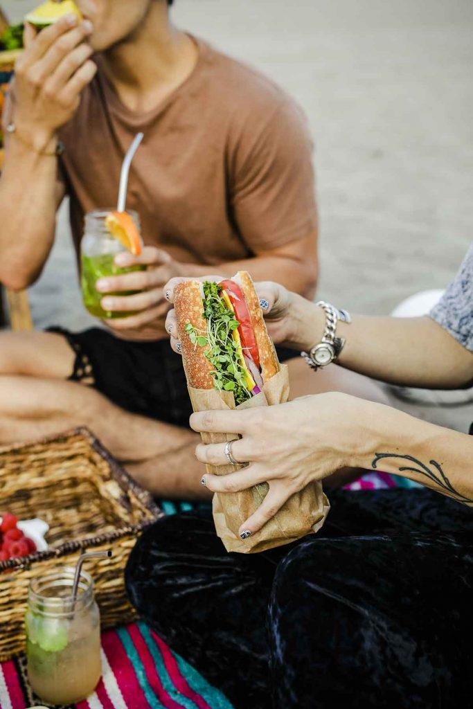 woman holding a sandwich wrapped in paper at picnic